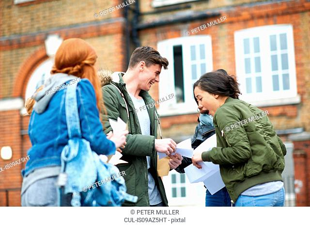 Happy male and female college students reading exam results on campus