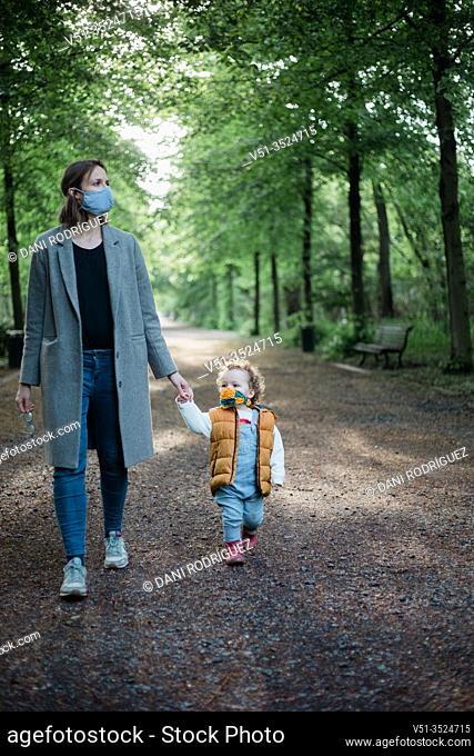 Mother and son walking in the park with mask during corona time