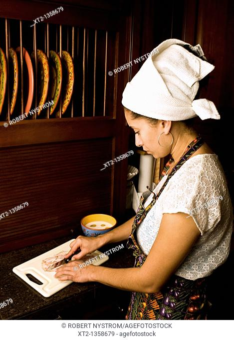 Woman in a kitchen cooking cutting meat on a board wearing an apron and hair towel