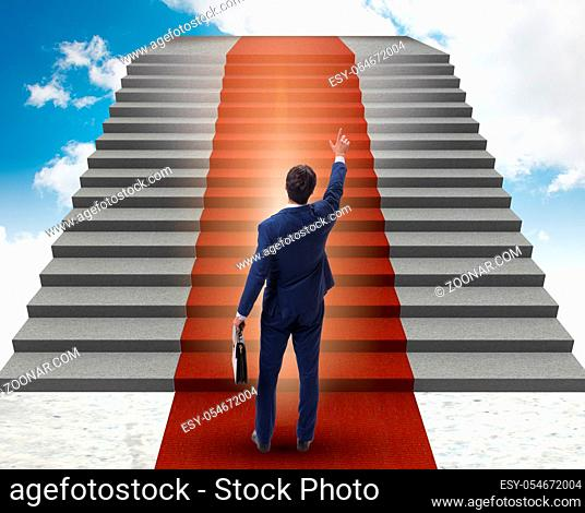 The young businessman climbing stairs and red carpet into sky