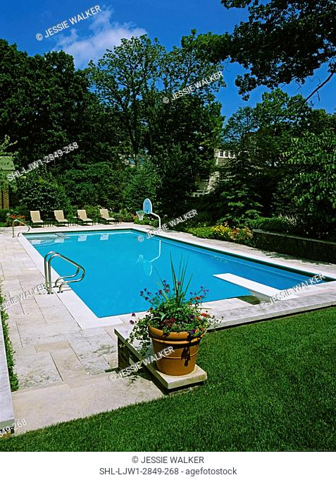 POOLS: View from elevated lawn area towards large 20' x 46' lap pool, retractable cover, Iowa limestone steps and patio, diving board, basketball hoop