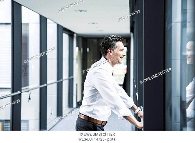 Smiling businessman looking out of window in office passageway