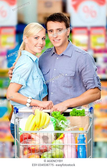 Half-length portrait of couple in the supermarket with cart full of food. Concept of consumerism and healthy food
