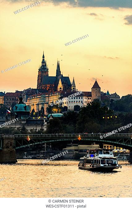 Czechia, Prague, view to castle and Charles Bridge with Vltava in the foreground at sunset