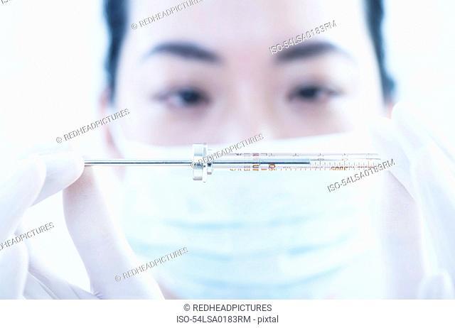 Doctor examining syringe