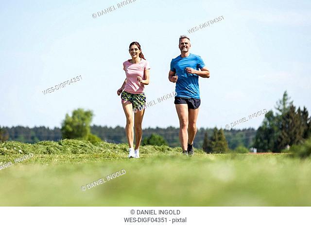 Couple running on field path