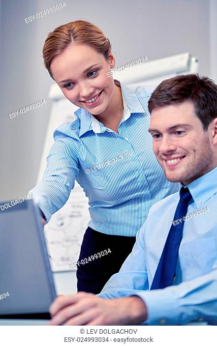business, people, technology and teamwork concept - smiling businessman and businesswoman with laptop computer meeting and talking in office