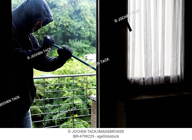 Symbol image of burglary, perpetrator tries to break into an apartment, picks up a window with a tool, Germany