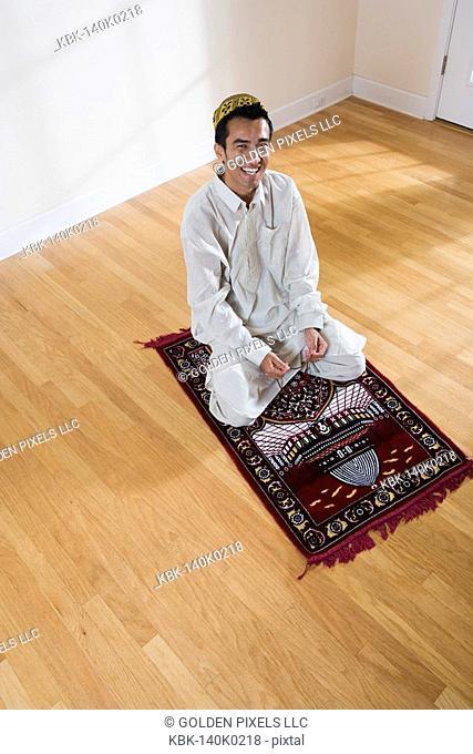 Portrait of a Muslim man praying on a prayer mat