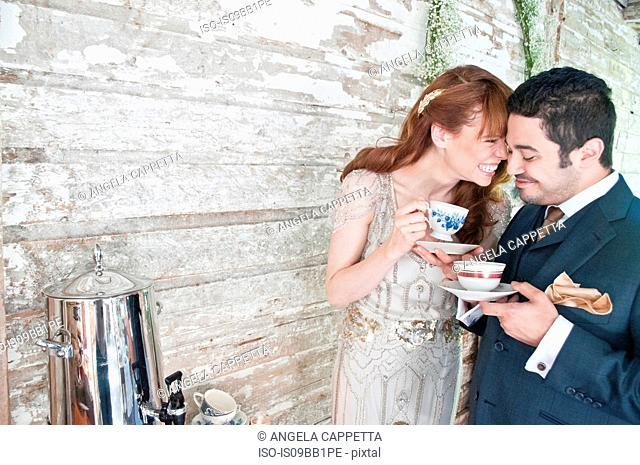 Bride and groom, drinking tea from tea cups, laughing