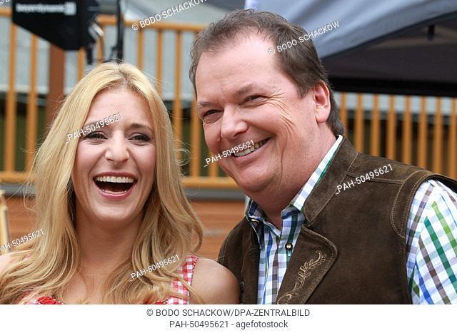Stefanie Hertel and the Austrian presenter Arnulf Prasch laugh during the rendezvous of artists at the folk music open air event 'Wenn die Musi spielt' (orig