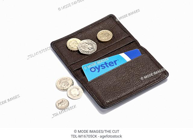 An Oyster card in a leather holder and British coins