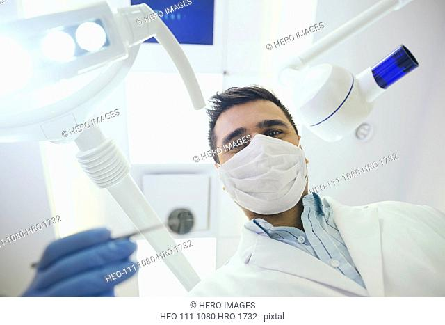 Portrait of dentist in surgical mask performing checkup