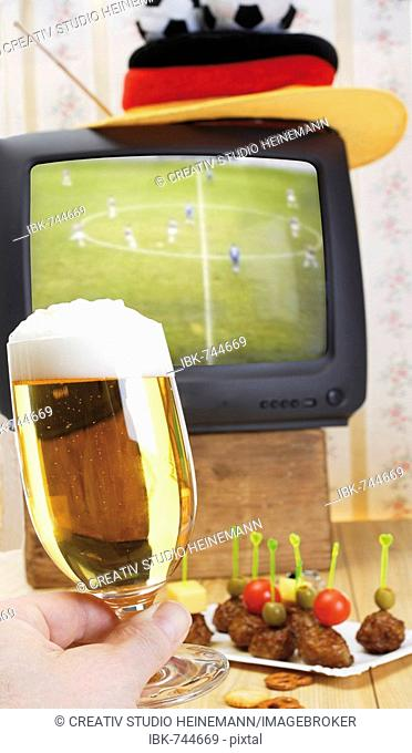 Retro football broadcast - TV broadcast of a game, football hat, tray of skewered meatballs and hand holding a glass of beer