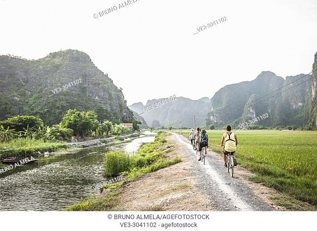 Tourists biking near Tam Coc in Trang An karst Landscape Complex (Ninh Binh province, Vietnam)