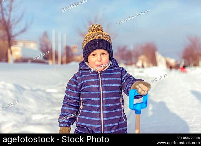A little boy in the winter in the city, in a blue jumpsuit and a warm yellow hat. In the hands of holding a spatula. Surprised resting in nature outside the...