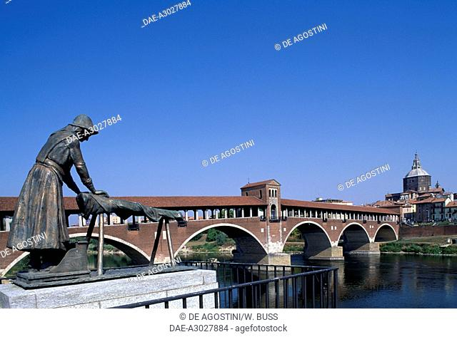 The covered bridge over the Ticino river, built in 1949 to the original 14th century structure, the Washerwomen Monument in the foreground, Pavia, Lombardy