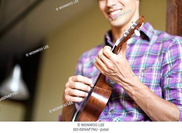 Young man playing ukulele