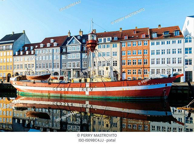 Moored boat with 17th century town houses on Nyhavn canal, Copenhagen, Denmark