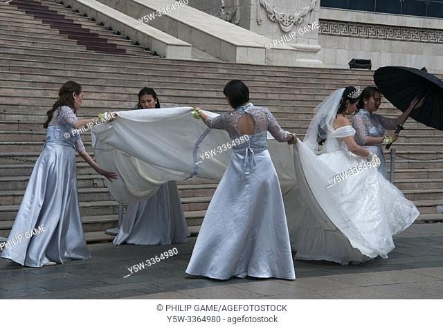 Members of a wedding party outside Parliament (Government) House on Sukhbaatar Square, Ulaanbaatar, Mongolia