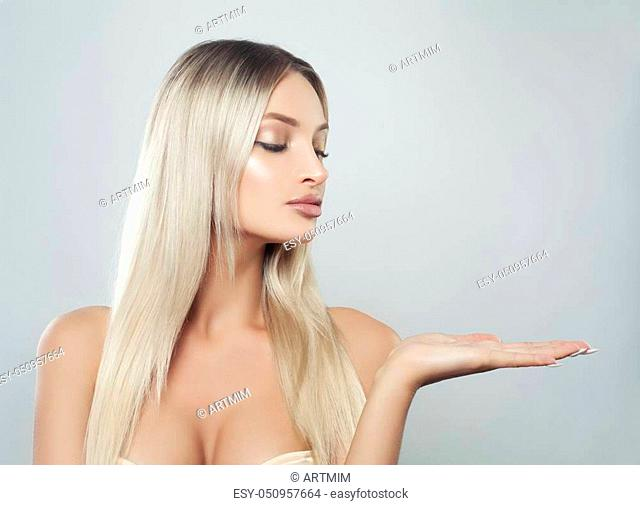 Perfect Young Woman with Clean Skin, Natural Makeup and Blonde Hair Showing Empty Copy Space on the Open Hand on White Background