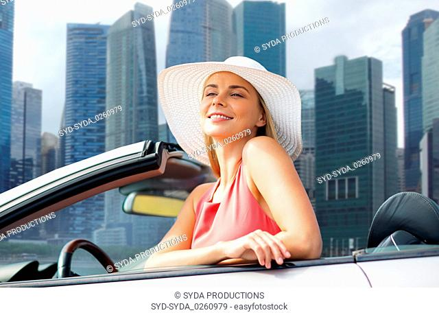 woman in hat in convertible car over singapore