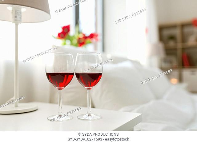 two glasses of wine on bedroom nightstand at home