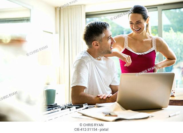 Smiling couple talking at laptop in morning kitchen