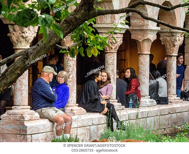 Perched on a wall with columns, multiracial visitors of different ages enjoy the Cuxa Cloister garden at The Cloisters Museum
