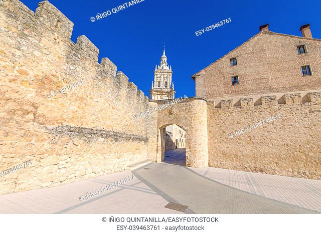 main public access to Burgo de Osma medieval town, with public street and tower of cathedral, landmark and monument from thirteenth century, in Soria, Spain