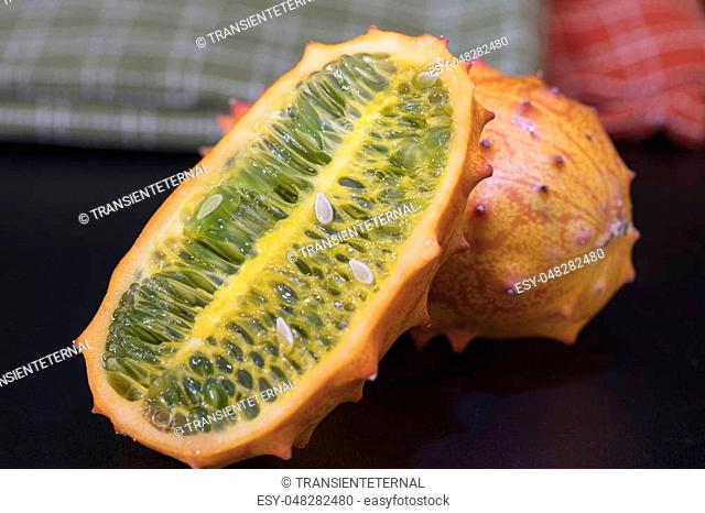Two orange and green Kiwano Fruits set on a table top with thorny skin