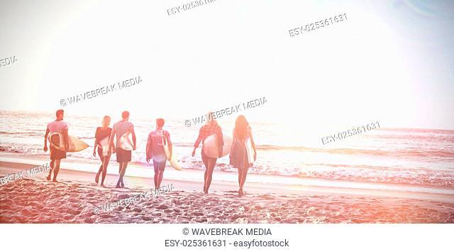 Happy friends walking with surfboards