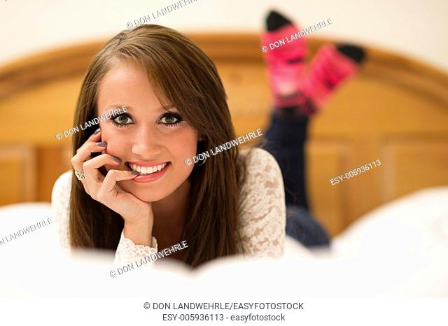 Attractive teenage girl resting her head in her hands lying on a bed