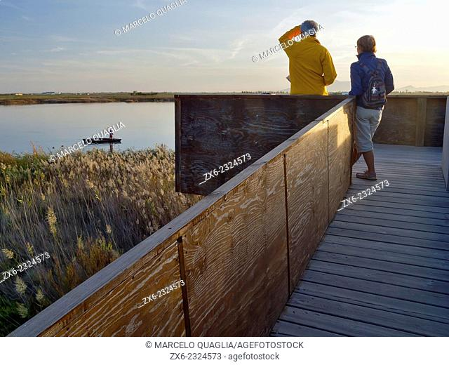 Hunter preparing decoy ducks while couple of tourists watch from observation tower at Les Olles petit lagoon. Ebro River Delta Natural Park, Tarragona province