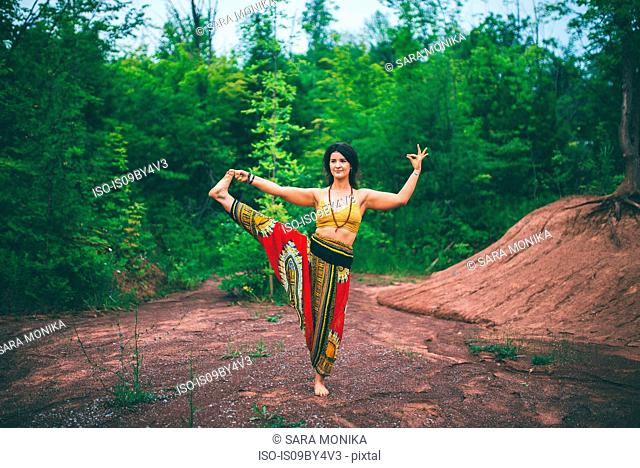Woman doing standing big toe pose in forest