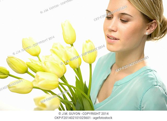 Woman looking down yellow tulip spring flowers isolated on white