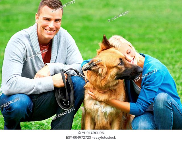 Young woman hugging her German Sheperd in a park while her boyfriend smilies at the camera