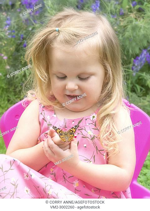 A little blonde girl sitting on a chair in a flower garden, gently holding a painted lady butterfly on her finger - Fraser Valley, British Columbia Canada