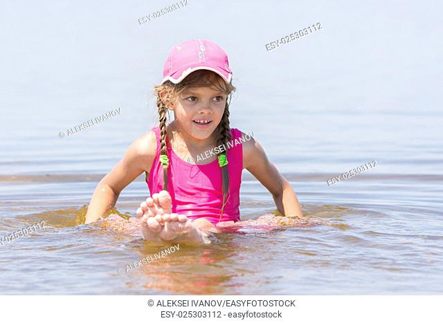 Girl in a cap sits on a shallow river in water