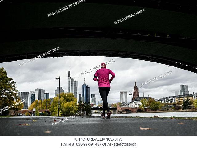 dpatop - 30 October 2018, Hessen, Frankfurt/Main: A female jogger runs under the Ignatz-Bubis-Bridge on the Frankfurt Main bank towards the skyline in autumn...