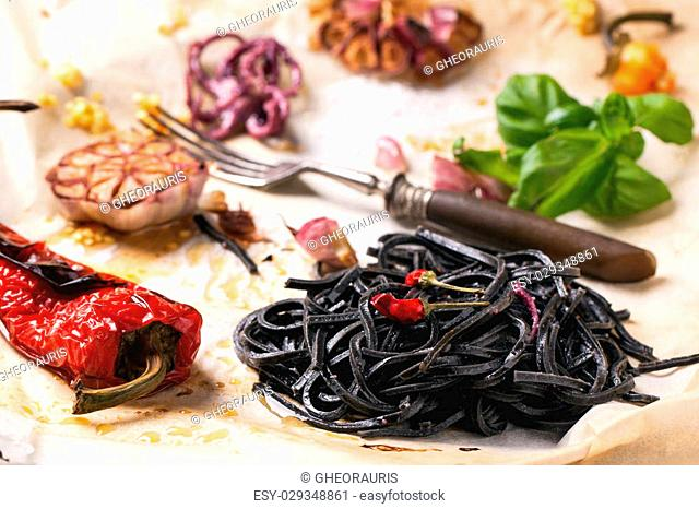 Black spaghetti served on crumpled baking paper with grilled paprika, garlic and fresh basil. See series