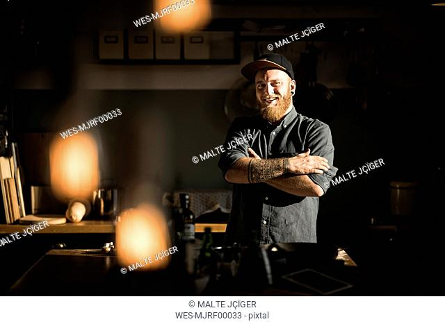 Proud hobby chef standing in his kitchen, with arms crossed