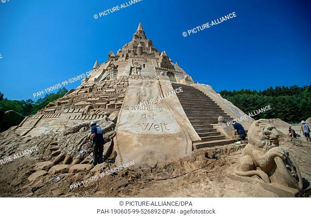 "05 June 2019, Mecklenburg-Western Pomerania, Binz: Sand artists have written the stroke """"The highest sand castle in the world"""" at the sand sculpture festival..."
