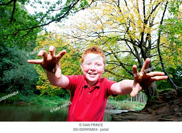 Boy pretending to be a monster in a woodland