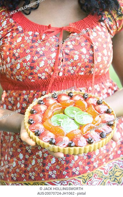 Mid section view of a woman holding a fruit pie