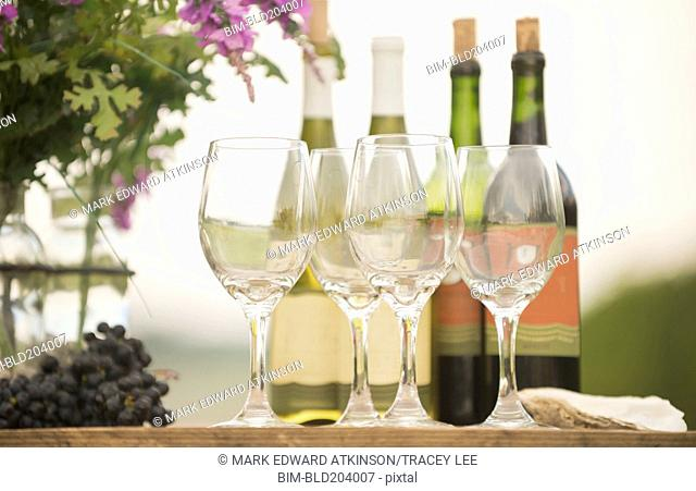 Wine bottle, grapes and glasses on table outdoors