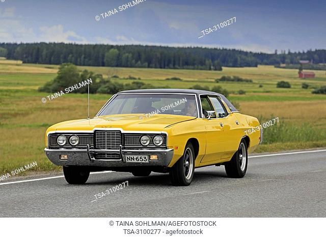 VAULAMMI, FINLAND - AUGUST 4, 2018: Yellow Ford LTD 4 door hardtop 2nd generation on road on Maisemaruise 2018 car cruise in Tawastia Proper, Finland