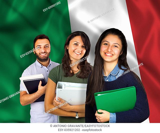 Couple of young students with books over italian flag