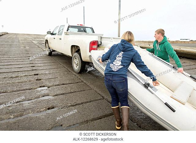 Young adults loading a rubber skiff onto a boat trailer on a boat ramp, Homer Spit, Kenai Peninsula, Southcentral Alaska