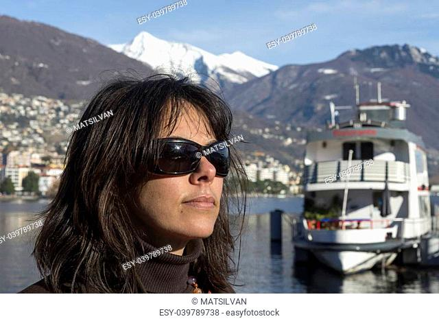 Woman with sunglasses and passenger ship and snow-capped mountain in background